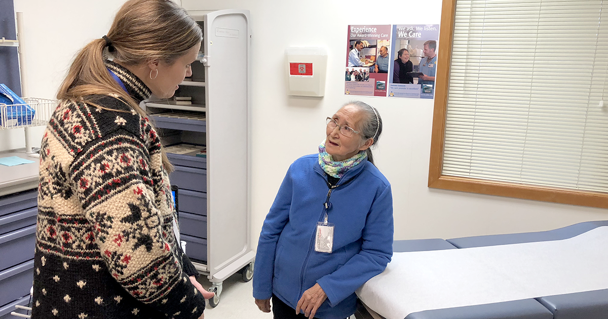 Kitti Cramer, EVP and Chief Legal & Risk Officer, discusses inpatient treatments with a behavioral health aide at Elana Alexie Memorial Clinic in Napaskiak, Alaska.