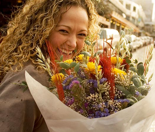 smiling woman holding large bunch of flowers